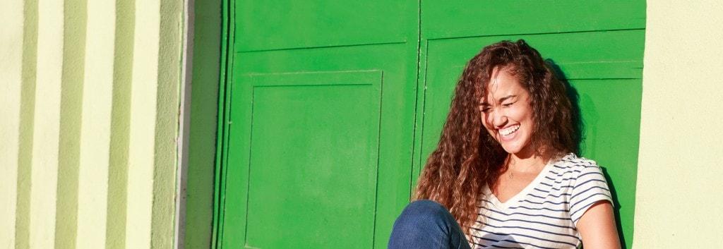 Mujer con cabello saludable rizado, riendo y divirtiéndose sentada en el suelo.