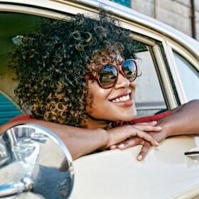 Mujer con cabello rizado sonriendo, con anteojos de sol, asomando por la ventanilla del auto.