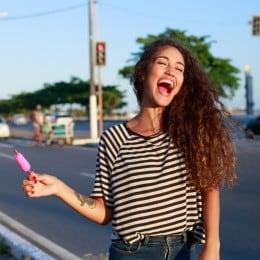 Una mujer alegre con cabello castaño rizado, comiendo un helado de palito y sonriendo.